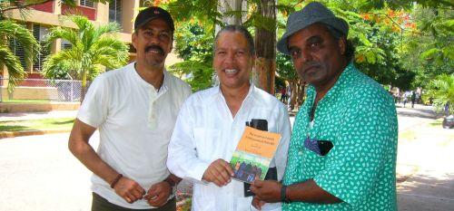 """Dr. Ravee recibe de manos del Dr. Manuel Jiménez (uasd) un ejemplar del libro """"Hay un país en el mundo y otros poemas de Don Pedro Mir"""". Les acompaña el editor de karateDOminicano"""